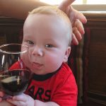 French baby drinking wine